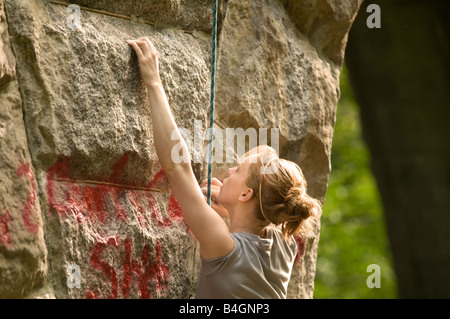 Female rock climber attempts to make her way up an old stone structure in the New England woods of Massachusetts - Stock Photo