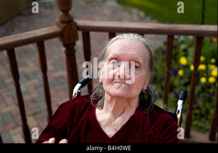 Elderly women sitting in a wheel chair outside on a deck - Stock Photo