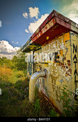 Some colorful graffiti is seen on this unusual building with a large pipe extruding from its side - Stock Photo