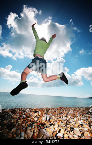 girl leaping on the beach - Stock Photo