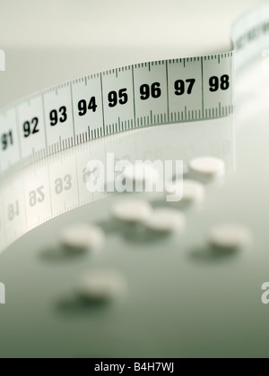 Close-up of pills and tape measure - Stock Photo