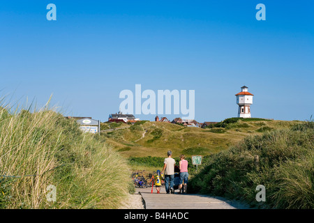 Family walking on boardwalk with lighthouse in background Langeoog Lower Saxony Germany - Stock Photo