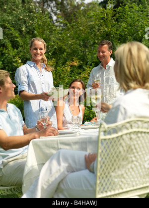 Five people celebrating at a garden party - Stock Photo