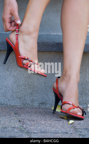 Female hand correcting the fit of her red high heel sandals - Stock Photo
