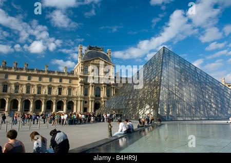 Tourists queue at the Pyramid entrance to the Musée du Louvre, Paris - Stock Photo