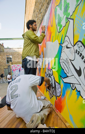 Young people painting a large mural of Nike 90 trainers on a wall at the Nike shop in Hoxton Hackney East London. - Stock Photo