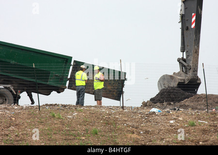 Waste Management Landfill workers with a backhoe placing dirt on trash in Menomonee Falls Wisconsin - Stock Photo