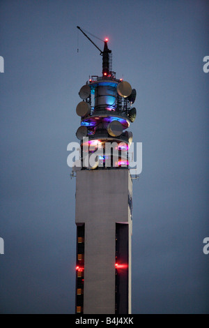 Communications devices lit up at night on top of the BT Tower in Birmingham UK - Stock Photo