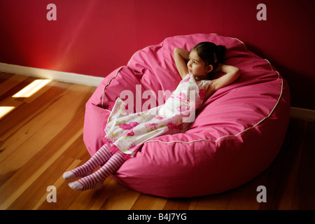 Girl 5 relaxes on pink bean bag - Stock Photo