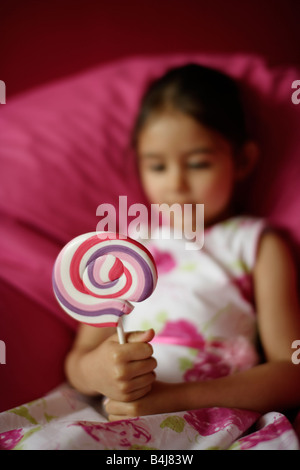 Girl 5 on pink bean bag with lollipop - Stock Photo
