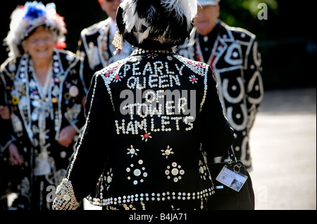 The London Pearly Kings & Queens Society: Back view of the Pearly Queen of Tower Hamlets walking towards fellow - Stock Photo