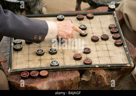 A close up of a male hand on a checkers board game in the Old Quarter Hanoi Vietnam - Stock Photo