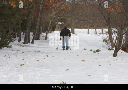 A man cross-country skiing in a snow-covered, forested area. - Stock Photo