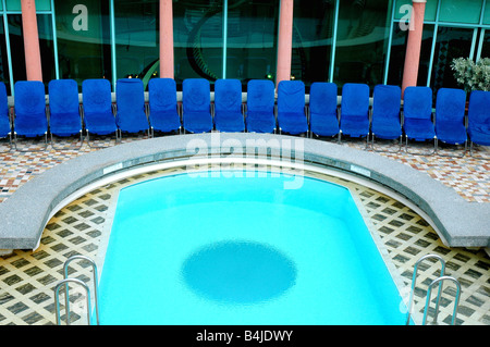 swimming pool and deck with lounge chairs aboard cruise ship adventure of the seas on royal caribbean cruise - Stock Photo