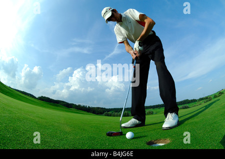 A wide and down view golf player driving a put close to the hole on the green golf course - France - Stock Photo