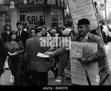 Spike Milligan actor with sandwich board handing out notices for a concert in which he and his wife Paddy star at - Stock Photo