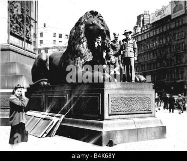 Soldiers on one of the lions in Trafalgar Square during WW2 VE Day victory celebrations - Stock Photo