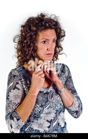 The gesture of patting or fondling her hair indicates insecurity and lack of self confidence in this woman in body - Stock Photo