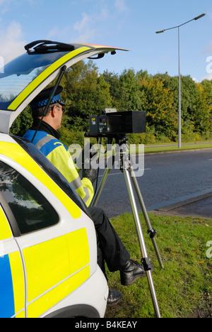 British traffic policeman operating a laser speed camera - Stock Photo