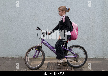 A 10 year old girl child wearing school uniform going to cycle to primary school on her pedal bike UK - Stock Photo