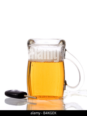 Beer mud filled with beer standing upside down near car keys Do not drink If you want to drive Your vehicle - Stock Photo