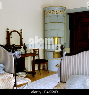 19th century bedroom with period furniture and ceramic stove in Swiss villa - Stock Photo