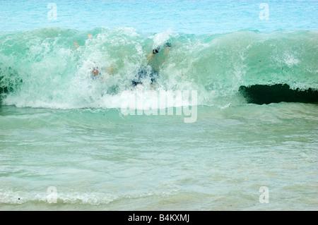 young boys body surfing at Little Maho Bay, St. John, USVI - Stock Photo