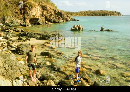 Boys playing on the rocks near a Lamshur Bay beach in St. John, USVI - Stock Photo