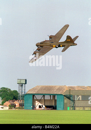 Wroughton Air Show August 1993 A Boeing B17 Flying Fortress Sally B flys low and banks over a hangar on the airfield - Stock Photo