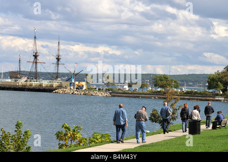 People walking path along Plymouth Harbor, MA, USA with the repilca of the pilgrim's ship the Mayflower in the background. - Stock Photo