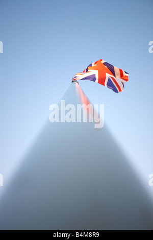 Union Jack National Flag blowing in the wind at the top of a flag pole in the United Kingdom. - Stock Photo