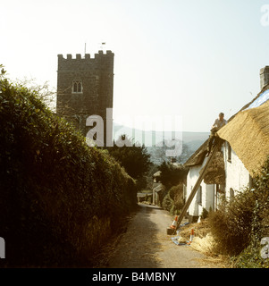 UK England Devon Bickleigh village traditional thatcher at work thatching cottage roof - Stock Photo