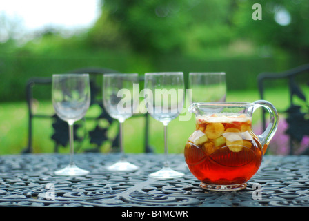 Jug of Pimms and glasses in an English country garden - Stock Photo