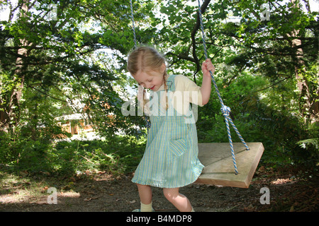 happy young beautiful girl wearing pretty dress outside in nature swinging on wooden swing from large green tree, - Stock Photo