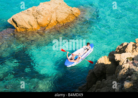 A man and a woman ride in a rubber boat between rocks  in the mediterranean bay of L'Escalet at the Cote d'Azur - Stock Photo