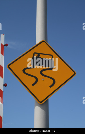 Close-up of Slippery When Wet Warning sign on bridge. - Stock Photo