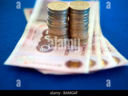 Pound coins on £20 pound notes - Stock Photo