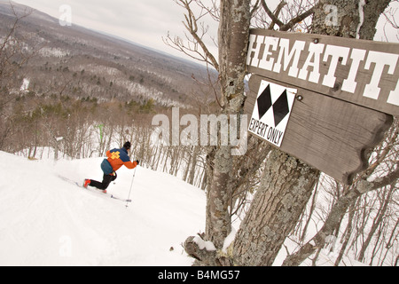A telemark skier enters a double black diamond run for experts only at Mount Bohemia ski resort in Michigans Upper - Stock Photo
