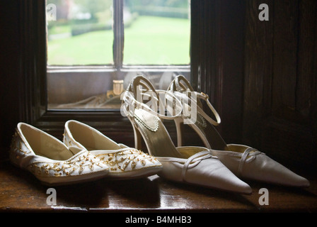 Horizontal close up of the bride's high heeled shoes and bridesmaid's beaded slip-ons on a window ledge before a - Stock Photo