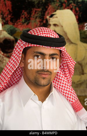 An Egyptian shopkeeper in Doha poses in front of a wall-carpet that displays the Emir - Stock Photo