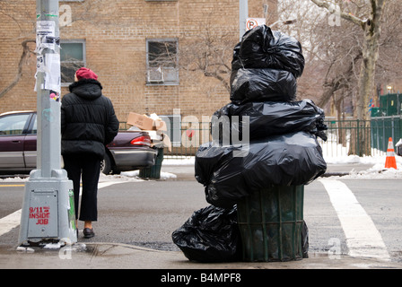 An overflowing garbage can next to '9/11 was an inside job' sign. - Stock Photo