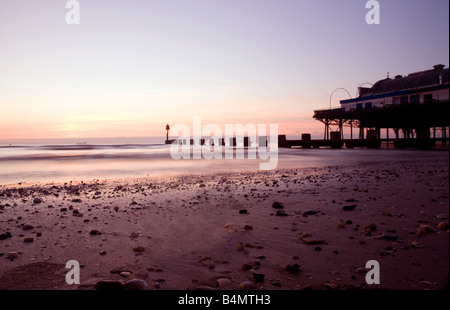 Sunrise on Cleethorpes beach with pier and beach in view in humberside near Grimsby south north east Lincolnshire - Stock Photo