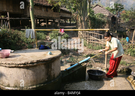 A woman gets water from a village pump in Mae Sot refugee camp Around 130 000 Burmese refugees have settled in Thailand - Stock Photo