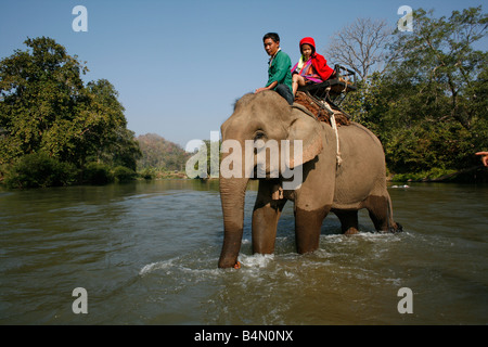 Members of the Longneck group cross a river by elephant Approximately 300 Burmese refugees in Thailand are members - Stock Photo