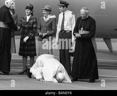 Pope John Paul II kneels down and kisses the ground at Cardiff airport on his visit to Wales L - Stock Photo