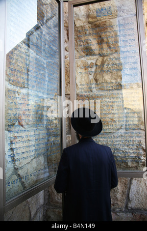 A Jewish man reads announcements posted near the Western wailing wall in Jerusalem - Stock Photo