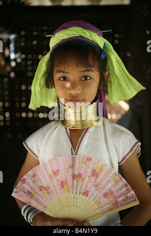 Portrait of a young Longneck girl with a fan Approximately 300 Burmese refugees in Thailand are members of the indigenous - Stock Photo