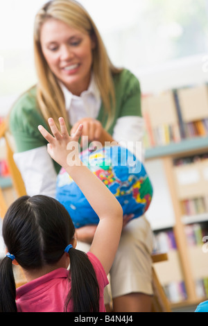 Teacher in class showing a globe with student volunteering in foreground (selective focus) - Stock Photo