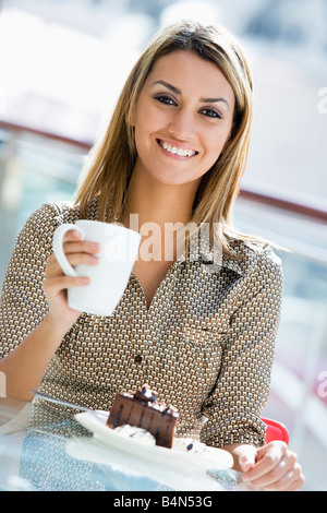 Woman at restaurant eating dessert and smiling (selective focus) - Stock Photo