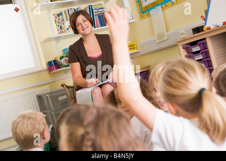 Teacher in class with student volunteering in foreground (selective focus) - Stock Photo